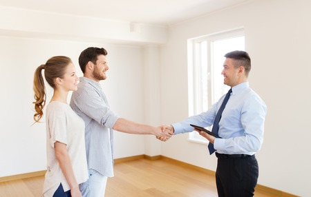 man and realtor shaking hands at new home Stock Photo