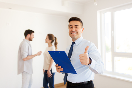 realtor with clipboard showing thumbs up Stock Photo