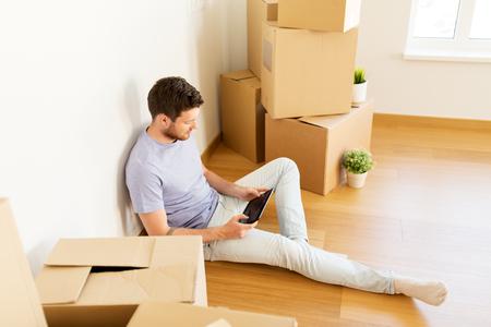 man met tablet pc en dozen verplaatsen naar nieuwe thuis