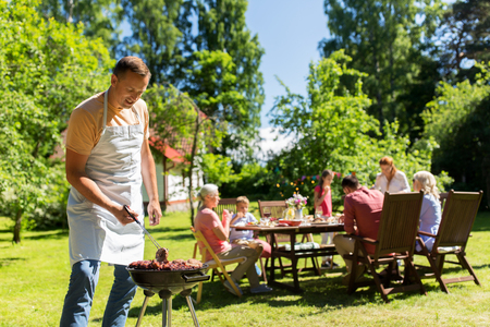 man cooking meat on barbecue grill at summer party Stock Photo - 84556895