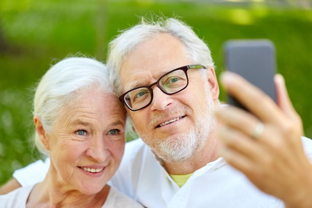 senior couple with smartphone taking selfie in summer Stock Photo