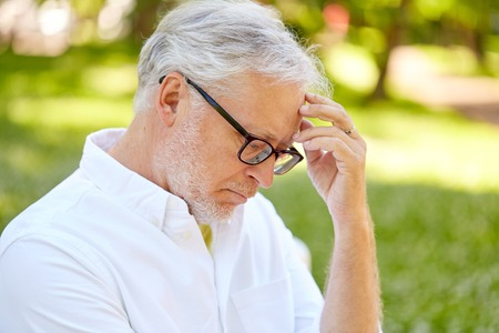 thoughtful senior man at summer park