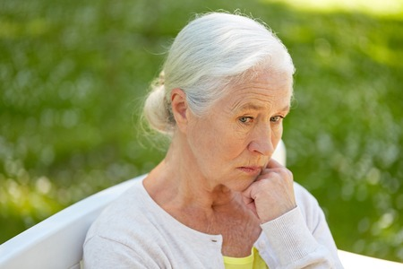 sad senior woman sitting on bench at summer park Archivio Fotografico