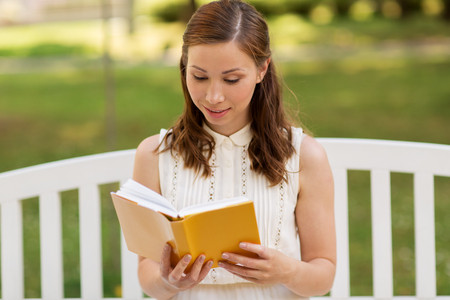 smiling young woman reading book at summer park Stok Fotoğraf