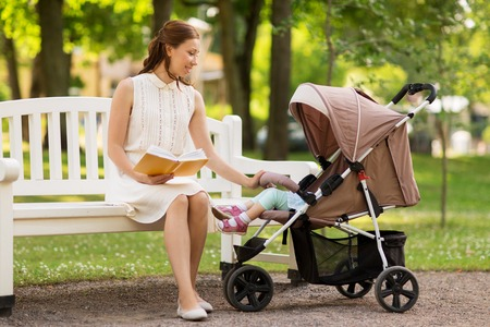 mother with child in stroller reading book at park Stock Photo