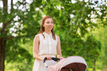 Happy mother with child in stroller at summer park Stock Photo - 84559289