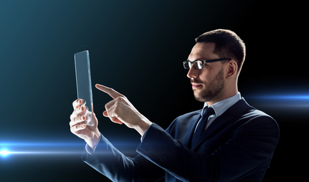 business, augmented reality and modern technology concept - businessman in glasses working with transparent tablet pc computer over black background