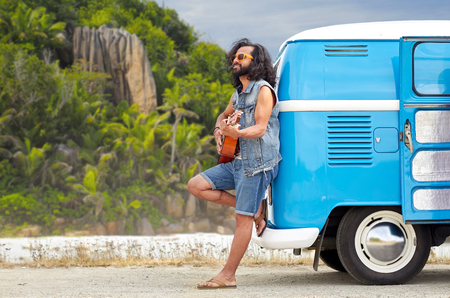 hippie man playing guitar at minivan car on island