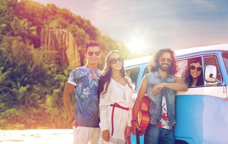 happy hippie friends at minivan car on island Stock Photo