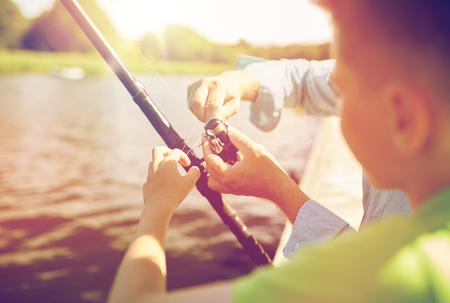 boy and grandfather with fishing rod on river Stock Photo