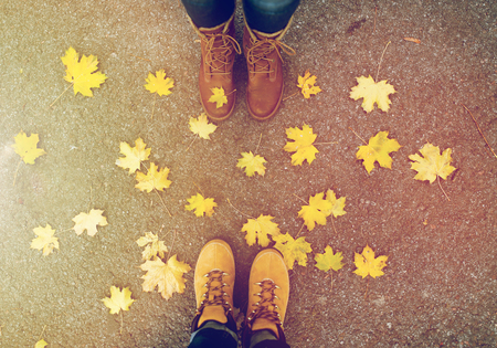 couple of feet in boots and autumn leaves Stock Photo