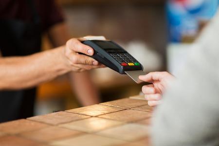 Manos con terminal de pago y tarjeta de crédito Foto de archivo - 84658506