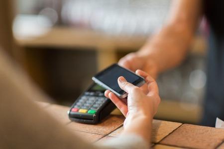 handen met betaalterminal en smartphone bij bar