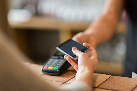 hands with payment terminal and smartphone at bar Banque d'images