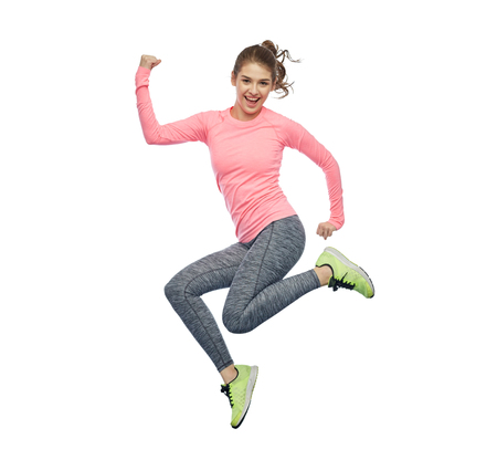 happy smiling sporty young woman jumping in air Archivio Fotografico