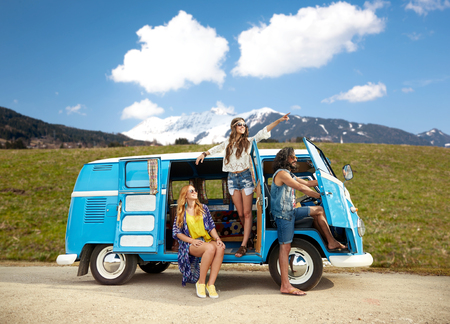 happy hippie friends in minivan car over mountains