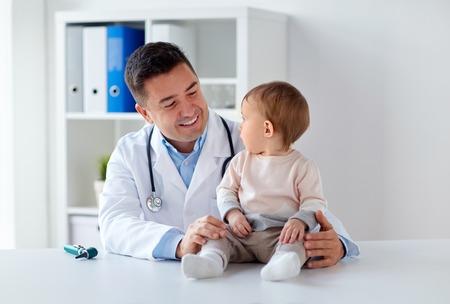 Glücklich Arzt oder Kinderarzt mit Baby in Klinik Standard-Bild - 84856852