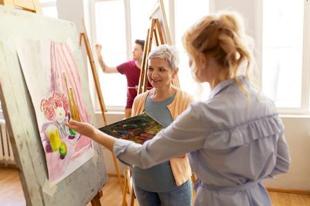 Artistas que discuten pintura en caballete en la escuela de arte Foto de archivo - 84856899