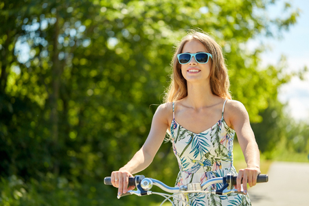 happy smiling young woman riding bicycle in summer
