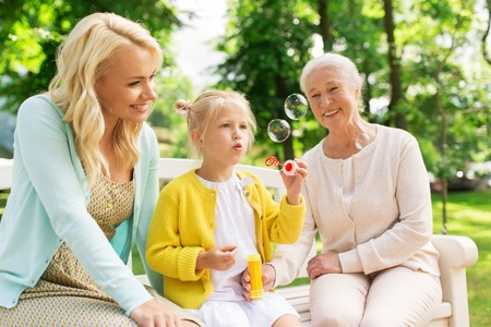happy family blowing soap bubbles at park Stock Photo