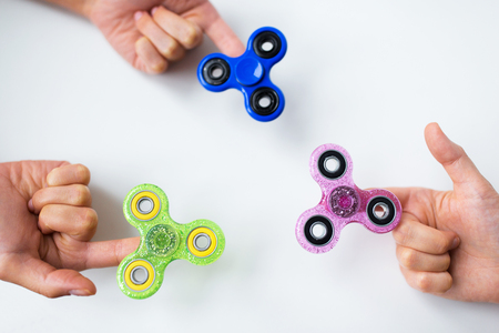 close up of hands playing with fidget spinners