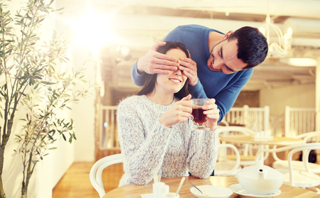 people, surprise and dating concept - happy couple drinking tea at cafe or restaurant Stock Photo