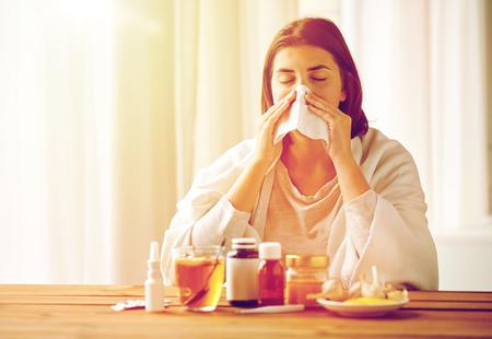 gezondheidszorg, griep, hygiëne, leeftijd en mensenconcept - de zieke vrouw met geneeskunde blazende neus aan document veegt thuis af