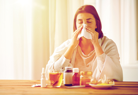 health care, flu, hygiene, age and people concept - sick woman with medicine blowing nose to paper wipe at home Reklamní fotografie - 84991925