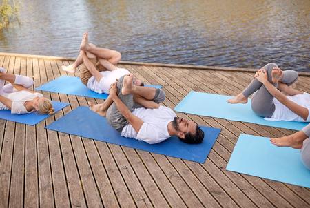 group of people making yoga exercises outdoors Banco de Imagens