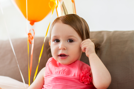 Concept de l'enfance, les gens et les célébration - heureuse petite fille portant la Couronne sur la fête d'anniversaire à la maison Banque d'images - 84991723
