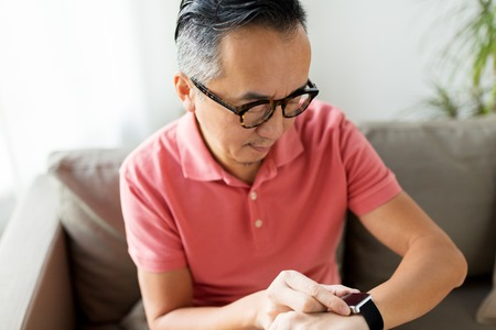close up of asian man with smart watch at home
