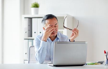 オフィスでノートパソコンで眼鏡をかけて疲れたビジネスマン