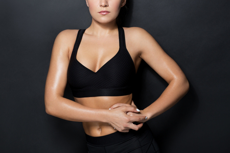 sport, fitness and people concept - close up of young woman in black sportswear posing in gym