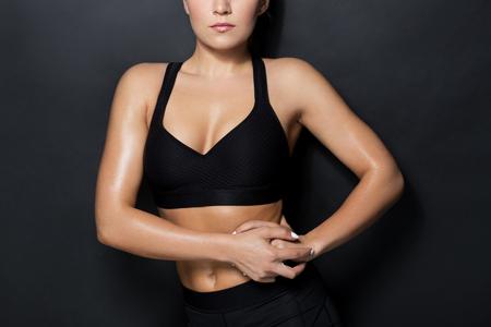 sport, fitness en mensenconcept - sluit omhoog van jonge vrouw in het zwarte sportkleding stellen in gymnastiek
