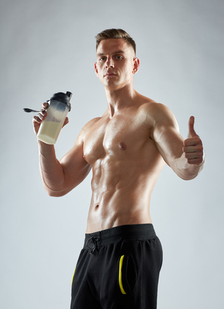 bodybuilder with protein shake showing thumbs up