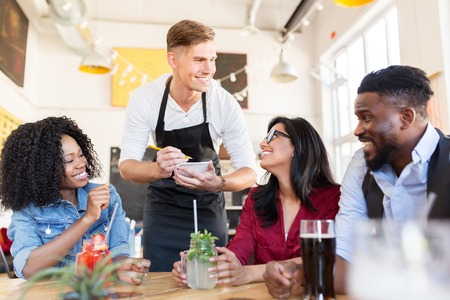 waiter and friends with menu and drinks at bar Stock Photo