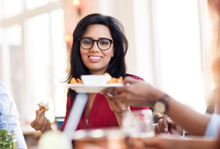 happy indian woman eating at restaurant Stock Photo