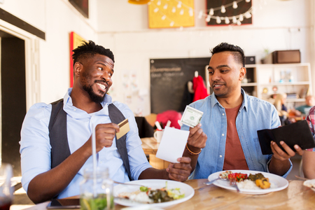 happy friends with money paying bill at restaurant