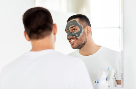 Young man with clay mask on face at bathroom
