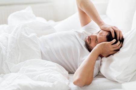 집에 침대에서 남자가 두통으로 고통 받고 스톡 콘텐츠