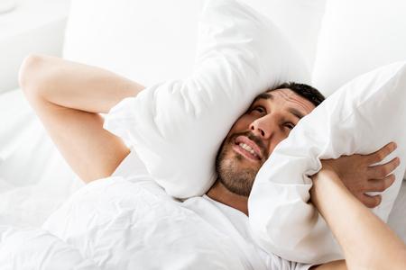 Mann im Bett mit Kissen, das unter Geräuschen leidet Standard-Bild - 84994487