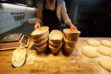 baker with baskets for bread dough at bakery