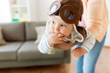 teething: happy mother with baby wearing pilot hat at home Stock Photo