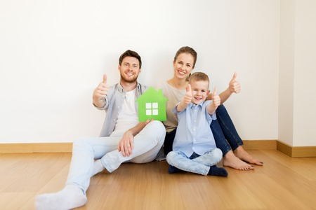 family with green house showing thumbs up at home Imagens - 85023780