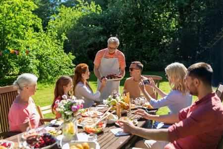 Famille heureuse ayant le dîner ou fête de jardin d'été