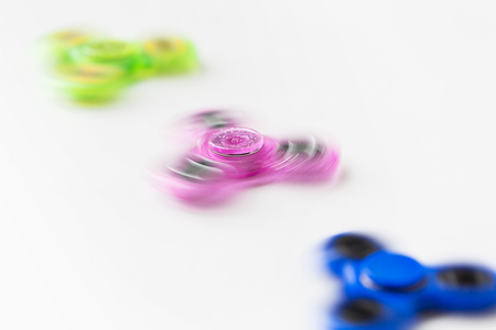 three spinning fidget spinners on white background