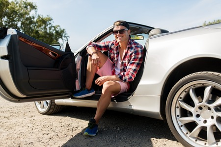 happy young man sitting in convertible car Stock Photo