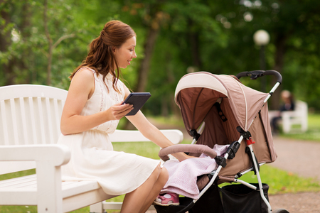 happy mother with tablet pc and stroller at park