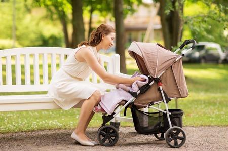 Feliz madre con el niño en el cochecito en el parque de verano Foto de archivo - 85005034