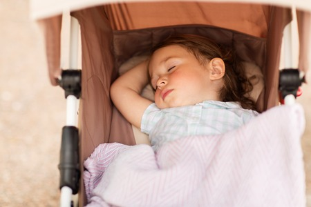 little child or baby sleeping in stroller outdoors Stock Photo